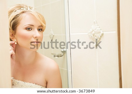 Beautiful blond bride in pearl sleeveless dress getting ready in front of a mirror in a bathroom - reflection - stock photo