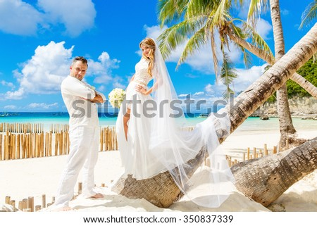 Beautiful blond bride in white wedding dress with big long white veil and with wedding bouquet and groom on shore sea under the palm trees. Tropical sea in the background. Summer vacation concept.