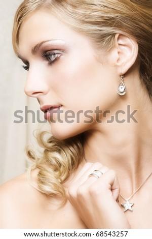 Beautiful Blond bride wearing diamond jewelery looking away - stock photo
