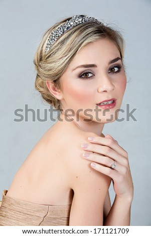 Beautiful blond bride wearing gold dress and diamond tiara as well as a solitare wedding ring on studio background