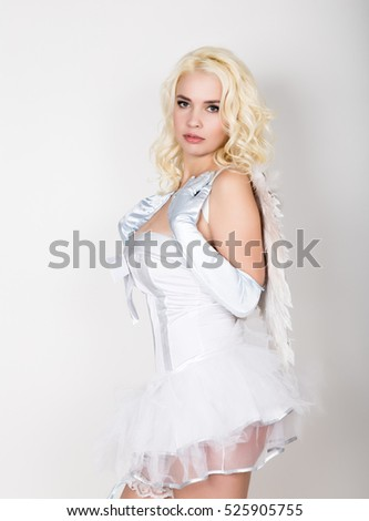 Beautiful blond bride wearing white dress with professional make-up and hairstyle, wings behind