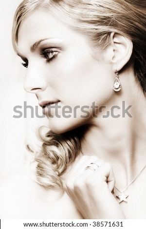 Beautiful Blond bride with blue eyes wearing diamond jewelery - stock photo