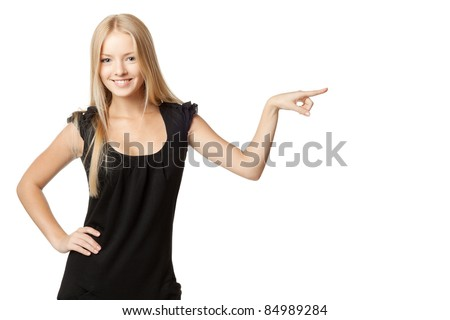 Beautiful blond business woman in black dress pointing at copy space over white background - stock photo
