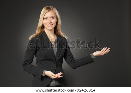 Beautiful blond business woman showing copy space over grey background - stock photo