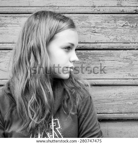 Beautiful blond Caucasian girl  teenager, closeup outdoor portrait over rural wooden wall - stock photo