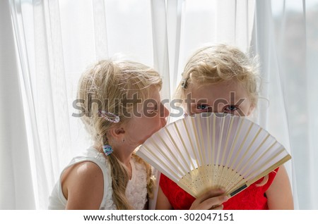 beautiful blond child with long hair in red and white dress among white curtain - stock photo