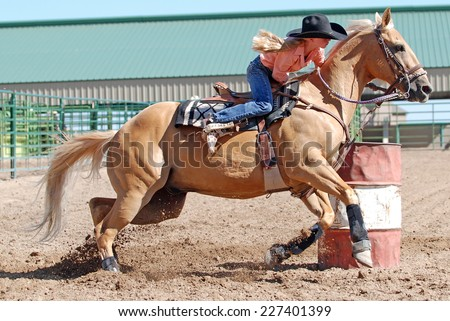 Beautiful blond cowgirl riding a palomino horse in a barrel race at a rodeo. - stock photo
