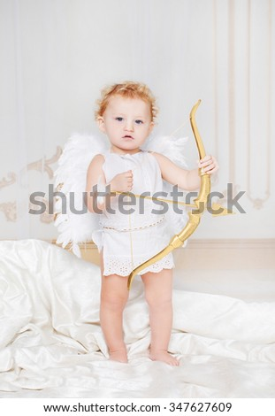 Beautiful blond curly toddler in a while lace dress with wings as a Cupid staying on the silk in the white room with gold moldings with golden bow in his hands. Saint Valentines Day celebration.   - stock photo