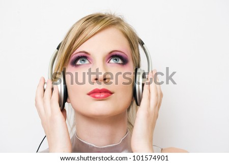 Beautiful blond electro pop girl enjoying music in headphones. - stock photo