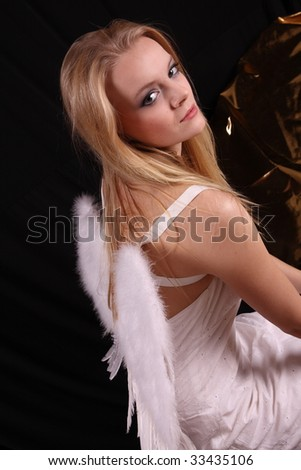 Beautiful blond fashion model posing in studio with angel wings