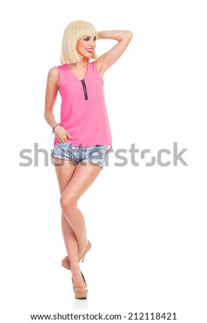 Beautiful blond fashion model posing. Smiling blond young woman in high heels and pink top standing on one leg and looking away. Full length studio shot isolated on white. - stock photo