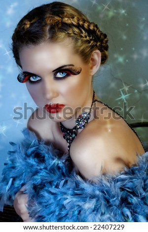 beautiful blond fashion model with feathers and long false lashes on star background