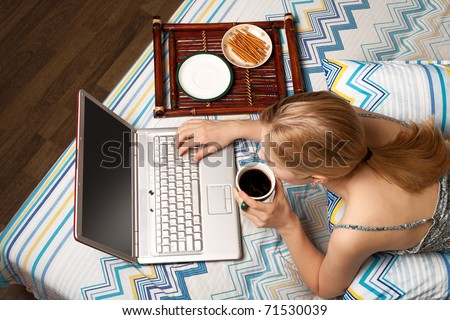 Beautiful blond female in bed with her laptop - stock photo