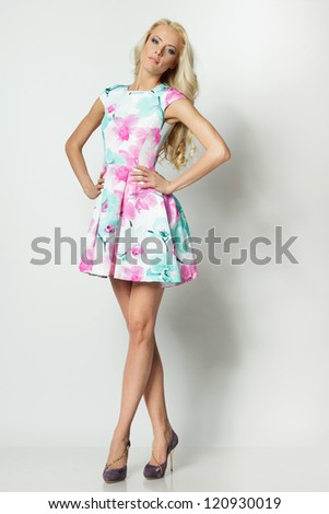 Beautiful blond female in full length posing in summer dress over white background