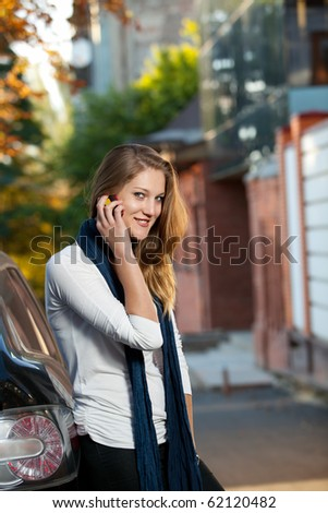 Beautiful blond female on the phone reclined against the car outdoors - stock photo