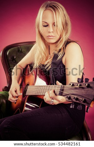beautiful blond female playing an acoustic guitar.