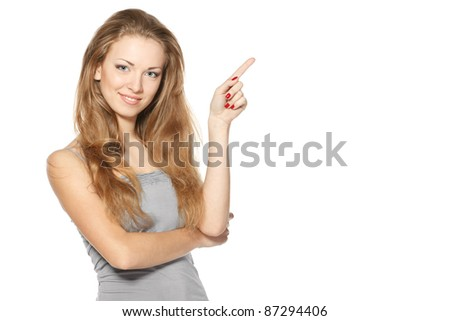 Beautiful blond female pointing at copy space over white background - stock photo