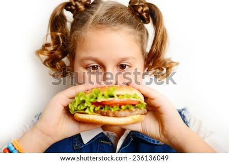beautiful blond girl, a teenager and a schoolgirl holding a hamburger on a white background - stock photo