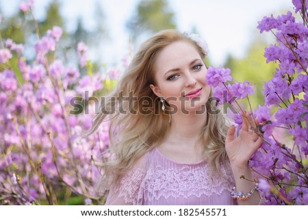 Beautiful blond girl among the spring flowering branches - stock photo