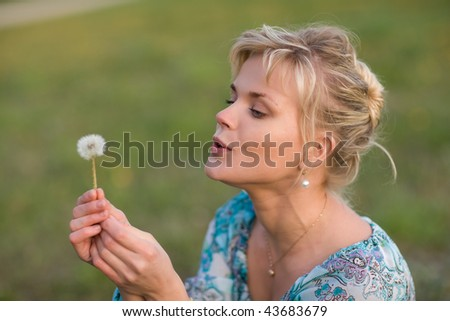 Beautiful blond girl blows dandelion seeds for luck