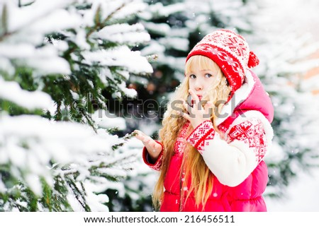 Beautiful blond girl blows with hands snowflakes in the snowy forest - stock photo