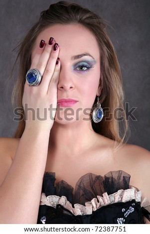 Beautiful blond girl covering her eye with hand and looking into the camera