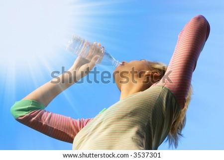 Beautiful blond girl dinking water - stock photo