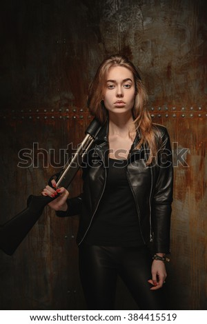 beautiful blond girl dressed in black with a gun near the metal wall with rusty streaks