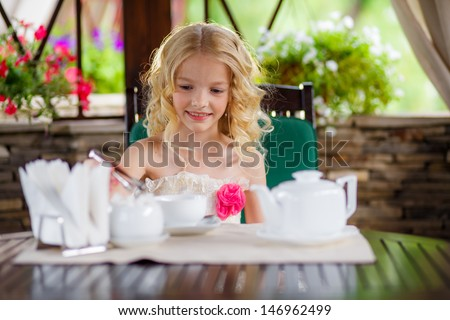 beautiful blond girl drinking tea in the gazebo on the shoulders stretched thin shawl - stock photo