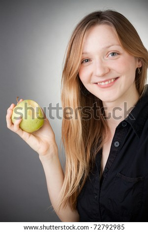 beautiful blond girl eating apple, with grey background - stock photo