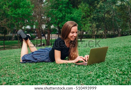 Beautiful blond girl freelancer working on the laptop lying on the grass summer day. Lifestyle