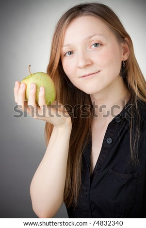 beautiful blond girl holding an apple, with grey background - stock photo