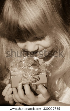 beautiful blond girl holding  present with ribbon sepia toned - stock photo