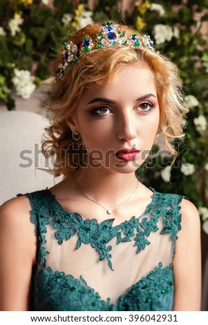 Beautiful blond girl in a crown, professional evening make-up. Beauty face. - stock photo