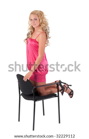 Beautiful blond girl in pink dress leaning on a chair