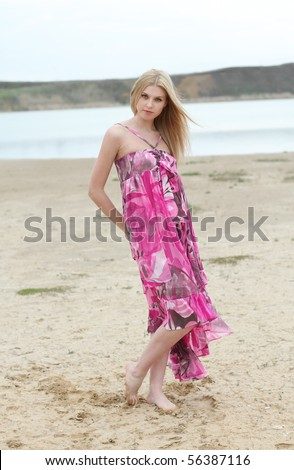 Beautiful blond girl in pink on the beach - stock photo