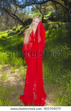 beautiful blond girl in red outdoors - stock photo