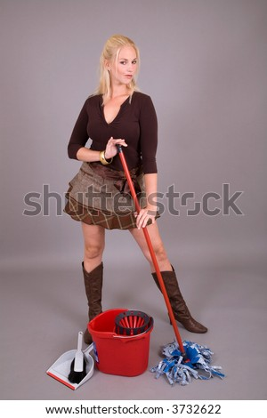 Beautiful blond girl in sexy skirt mopping the floor - stock photo