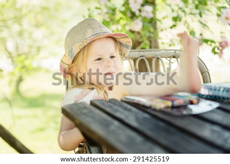Beautiful blond girl in the garden at sunny summer day - stock photo