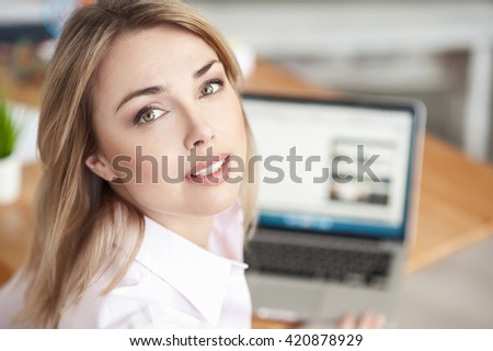 Beautiful blond girl is working on a computer - stock photo