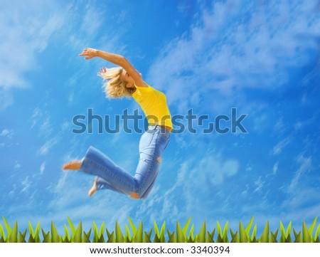 Beautiful blond girl jumps over green grass - stock photo