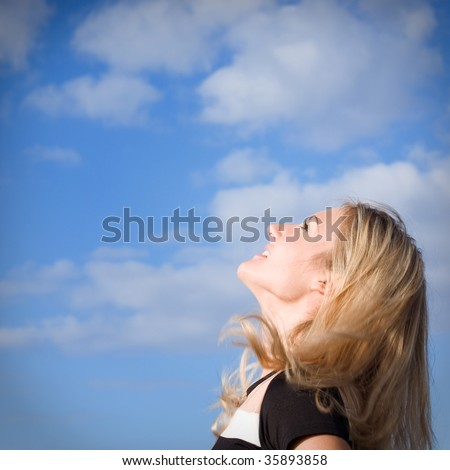 beautiful blond girl looking up to a blue cloudy sky - stock photo