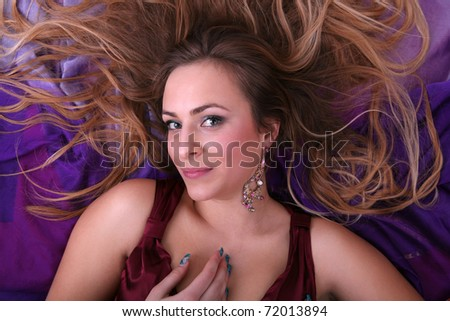 Beautiful blond girl lying on her back and looking into the camera