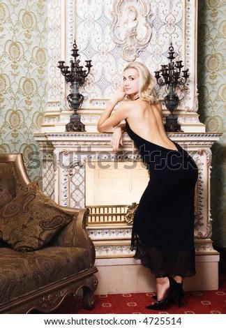 Beautiful blond girl near the fireplace - stock photo