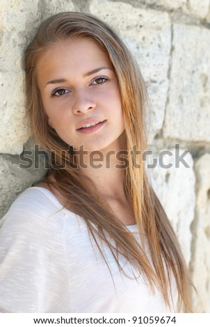 Beautiful blond girl outdoors against the sea - stock photo