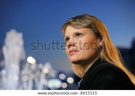 Beautiful blond girl over blue sky at sunset - stock photo