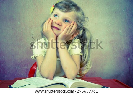 beautiful blond girl over open book - stock photo