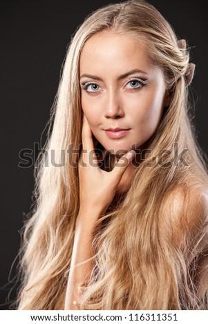 Beautiful blond girl posing. Dark  background. - stock photo
