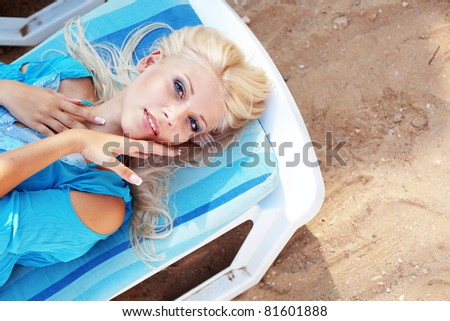 Beautiful blond girl relaxing on beach bad