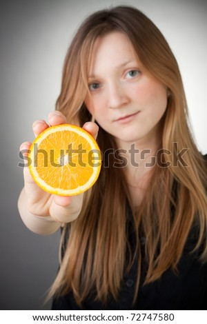 beautiful blond girl showing a half orange, with grey background - stock photo
